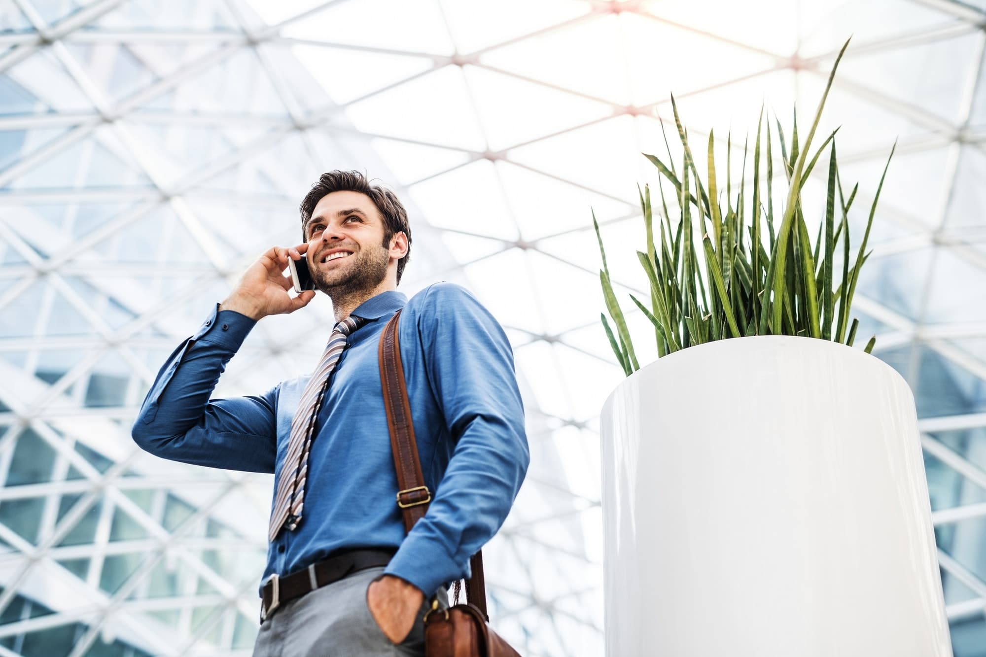 A young businessman with smartphone, making a phone call. Copy space.