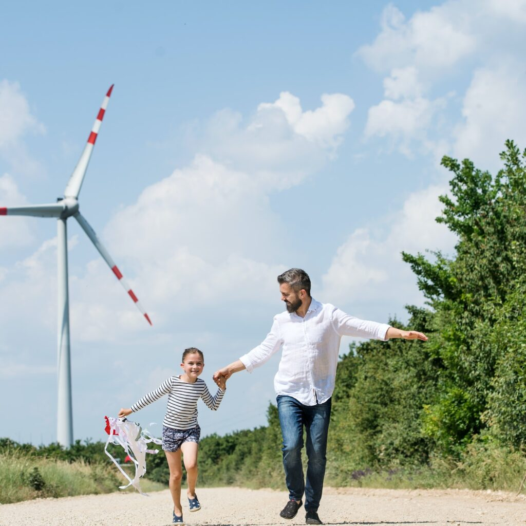 Mature father with small daughter on field on wind farm, running